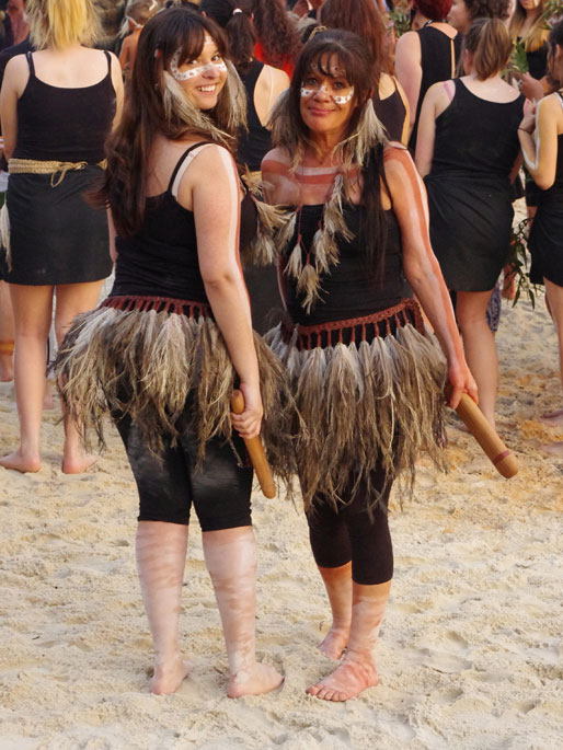 Two women wearing emu feather skirts, emu feather headpieces and holding wooden clapsticks stand in front of a crowd of people.
