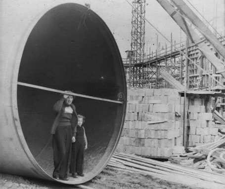Photograph of a woman and a young girl standing inside the open end of a very large pipe at a building site.