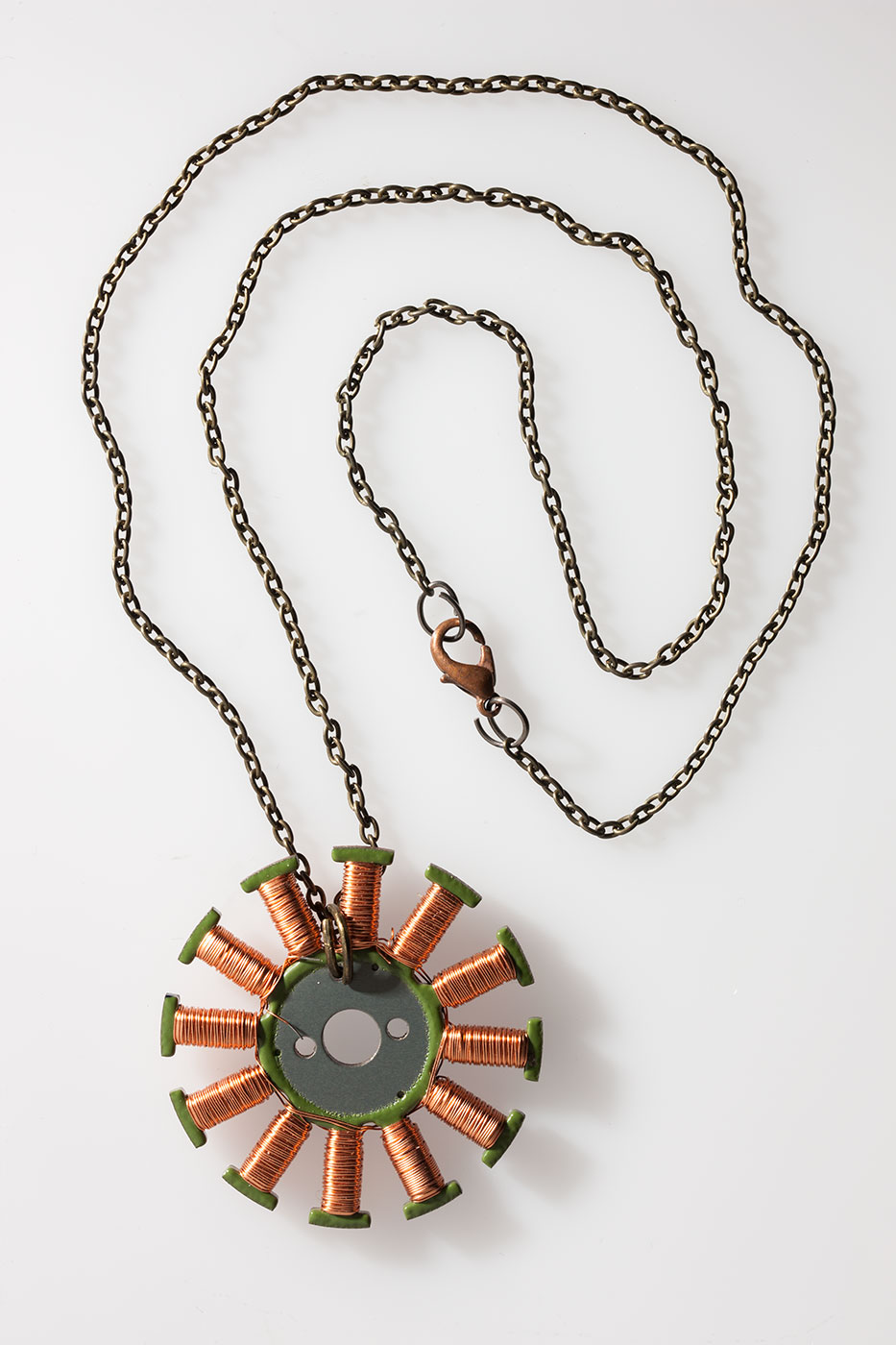 A circular metal pendant with green coloured t-shapes coiled with copper wire radiating from the centre, on a metal chain. - click to view larger image