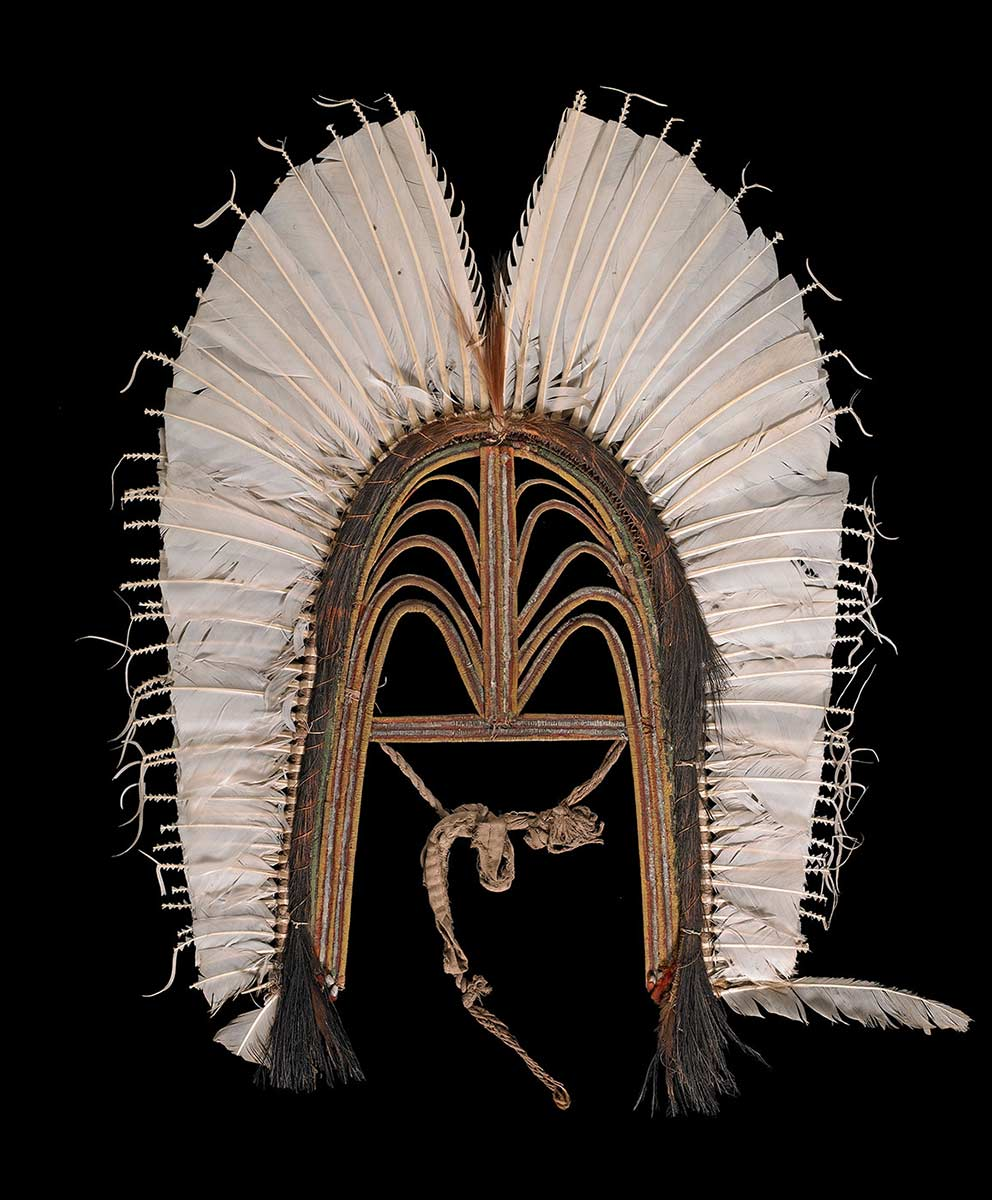 Headdress made of an open-work frame of bound cane with white feathers round the edge. Cassowary plumes are bound round the junction. The frame is painted red, yellow and white. - click to view larger image