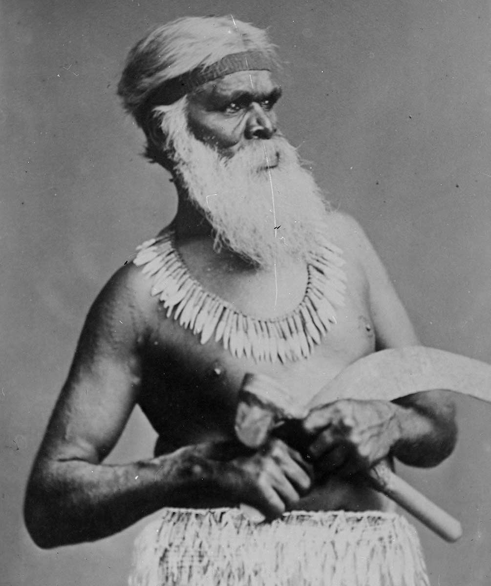 Black and white portrait of an Indigenous Australian man in traditional clothing. - click to view larger image