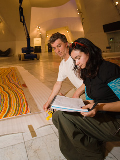 A colour photograph showing two museum staff inspecting a large Indigenous painting. The painting, has been rolled out on the floor and has vibrant multicoloured stripes. A high-lift crane is visible in the background.