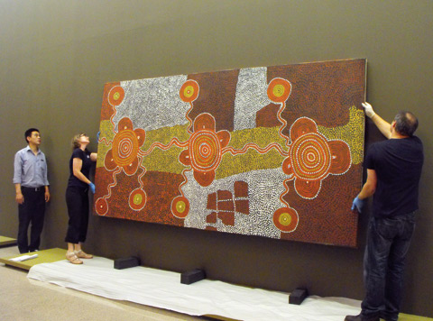 A colour photograph of three museum staff installing a large painting in an exhibition. The painting features traditional patterns in ochres, browns, yellows and white. Two people wearing gloves hold the painting up off the floor. Three support blocks can be seen on the floor underneath the painting. The wall in the background where the painting will be hung is olive green.