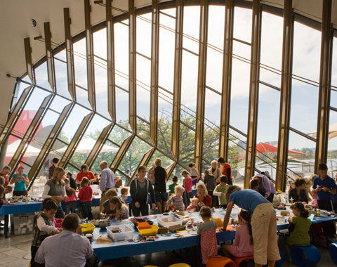A colour photograph of children and their parents engaged in a workshop in what appears to be a museum. Two long tables are visible, running slightly diagonally from left to right. On each table are tubs of craft materials. Some of the materials are spread out on each table. Young children sit or stand around each table, apparently making objects from the materials. Some parents are also around the tables, assisting the children. In the backgound is a large window which towers above the tables. It has large girder-like bracing structures running across it. Outside can be seen a tree and some large shade umbrellas.