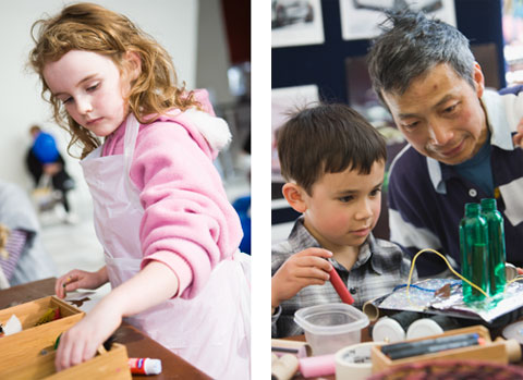 Two colour photographs, side by side. The left side photograph shows a young girl engaged in a craft activity reaching into a box that contains craft materials. The photograph on the right shows a father and his son holding what appears to be a large marker pen or crayon in his right hand. Both are looking at a craft construction composed of cardboard, aluminium foil and two small green plastic bottles.