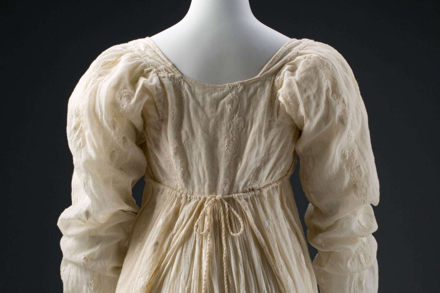 Back view of a muslin dress with an embroidered leaf pattern. - click to view larger image