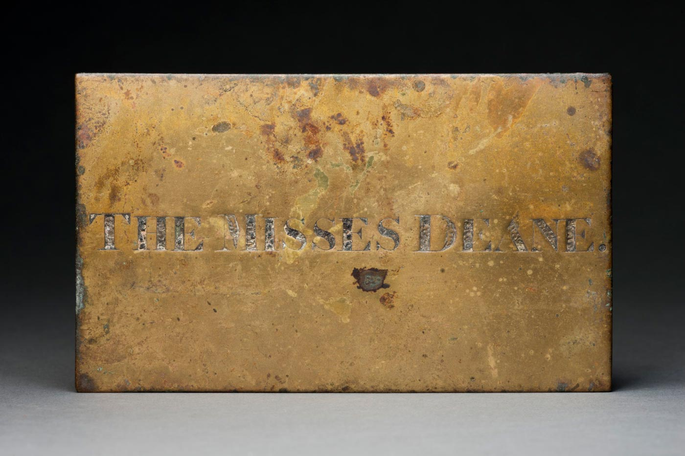 Brass name plate with the letters in capitals 'THE MISSES DEANE' engraved in the middle, showing signs of wear with several dents and metal clasps at the edges for hanging.