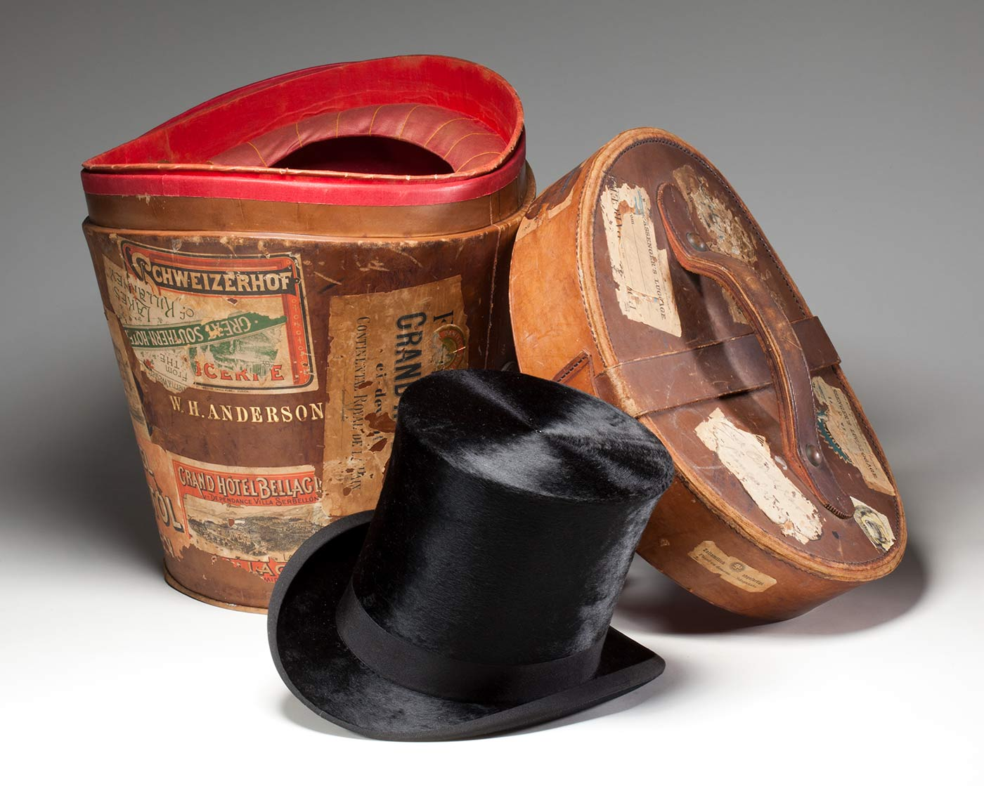 Black top hat made by J Woodrow & Sons, London, with hat box covered in travel stickers, featuring the inscription 'W. H. ANDERSON'.