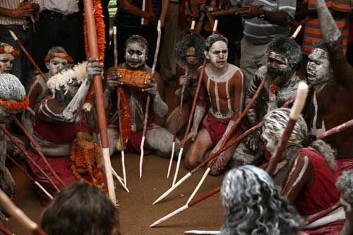 A colour photograph of eleven Australian Indigenous people sitting in a circle. Each of them has traditional body and face markings. Some have white pigment in their hair. Many hold long spears that are painted red and white. The tips of the spears rest on the floor. Behind the group stand other people, only visible from the waist down.