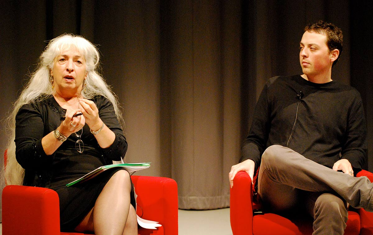 An elderly woman and a young man are sitting in red chairs on a stage in discussion.