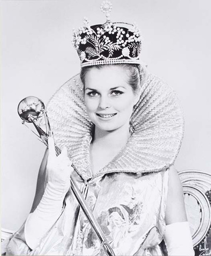 Miss Australia 1971, June Wright holding the sceptre wearing the crown a long, gold, frilled-collar, sleeveless cape and white gloves - click to view larger image