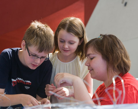 Two young children and a woman intently engaged in a craft activity. Loops of string are out of focus in the foreground; in the background the red and white walls of the Museum's Hall are visible.