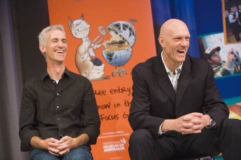 David Pope and Peter Garrett sit laughing, with crossed hands, in front of a banner showing a caricature of Kevin Rudd as a kangaroo, barbecuing an Australia-shaped steak.