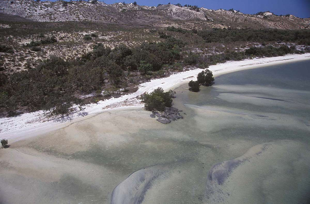A colour photograph of a section of coastline. In the foreground is shallow water, under which can be seen streaks of sand. A narrow white sand beach runs diagonally across the middle of the photograph. In the upper part of the image is the coastline, which is made up of rocky outcrops and areas of vegetation.  - click to view larger image