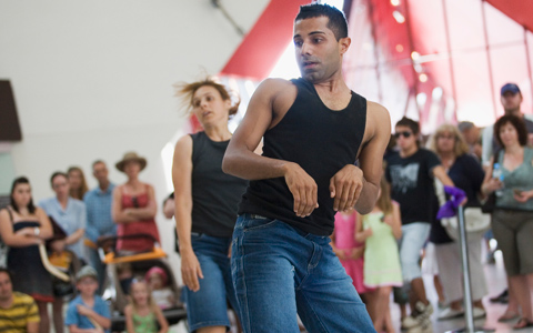 An image of two dancers, a man closer to the camera and a woman in the middle ground of the image. Behind them and slightly out of focus an audience circles around them.
