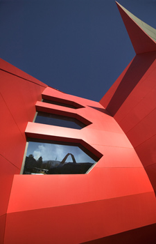 Detail of a red outside wall of the Museum's building looking up along the wall. One of the windows in the wall reflects the image of the Loop.
