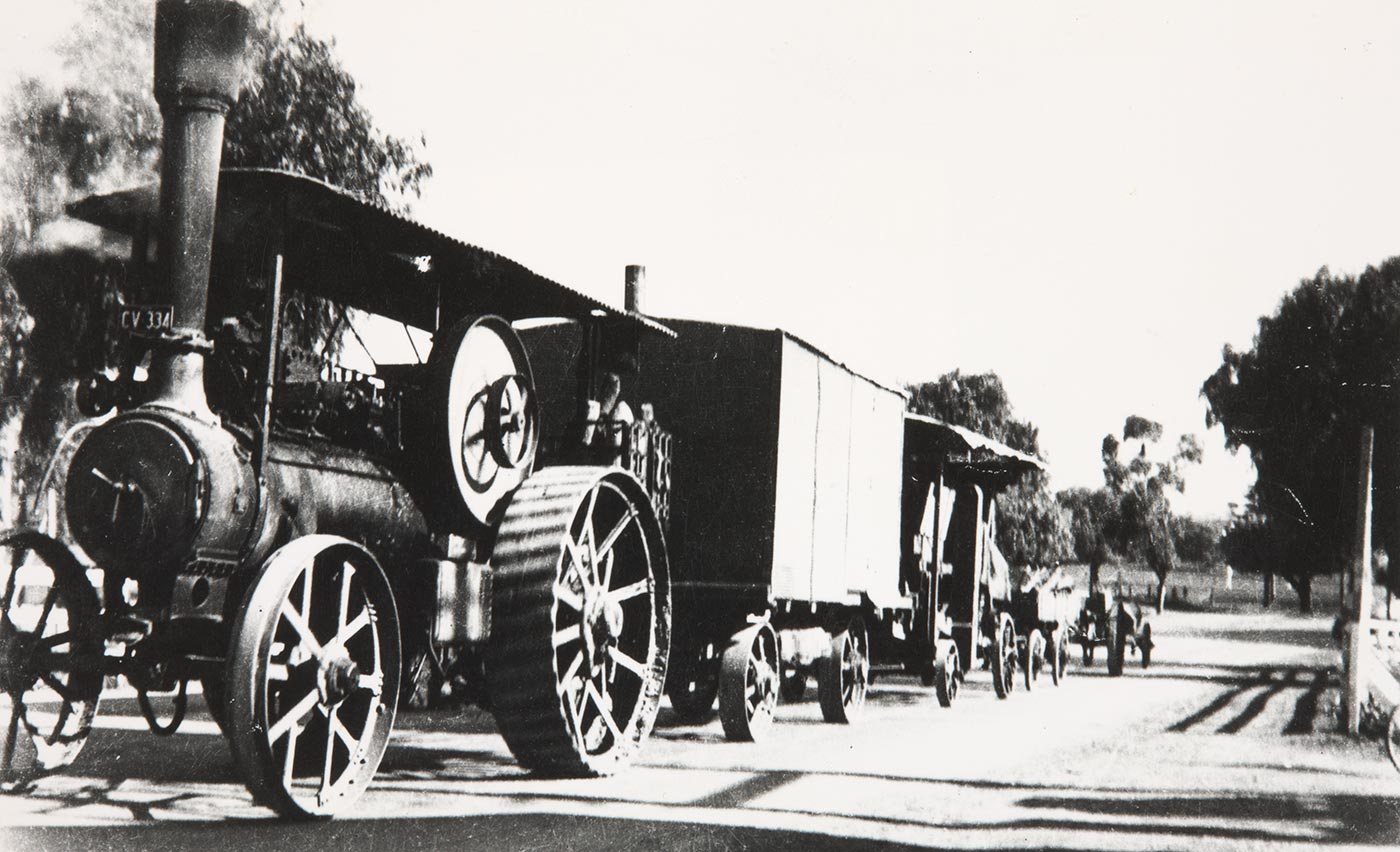A steam-powered vehicle, towing several carriages on a street. - click to view larger image