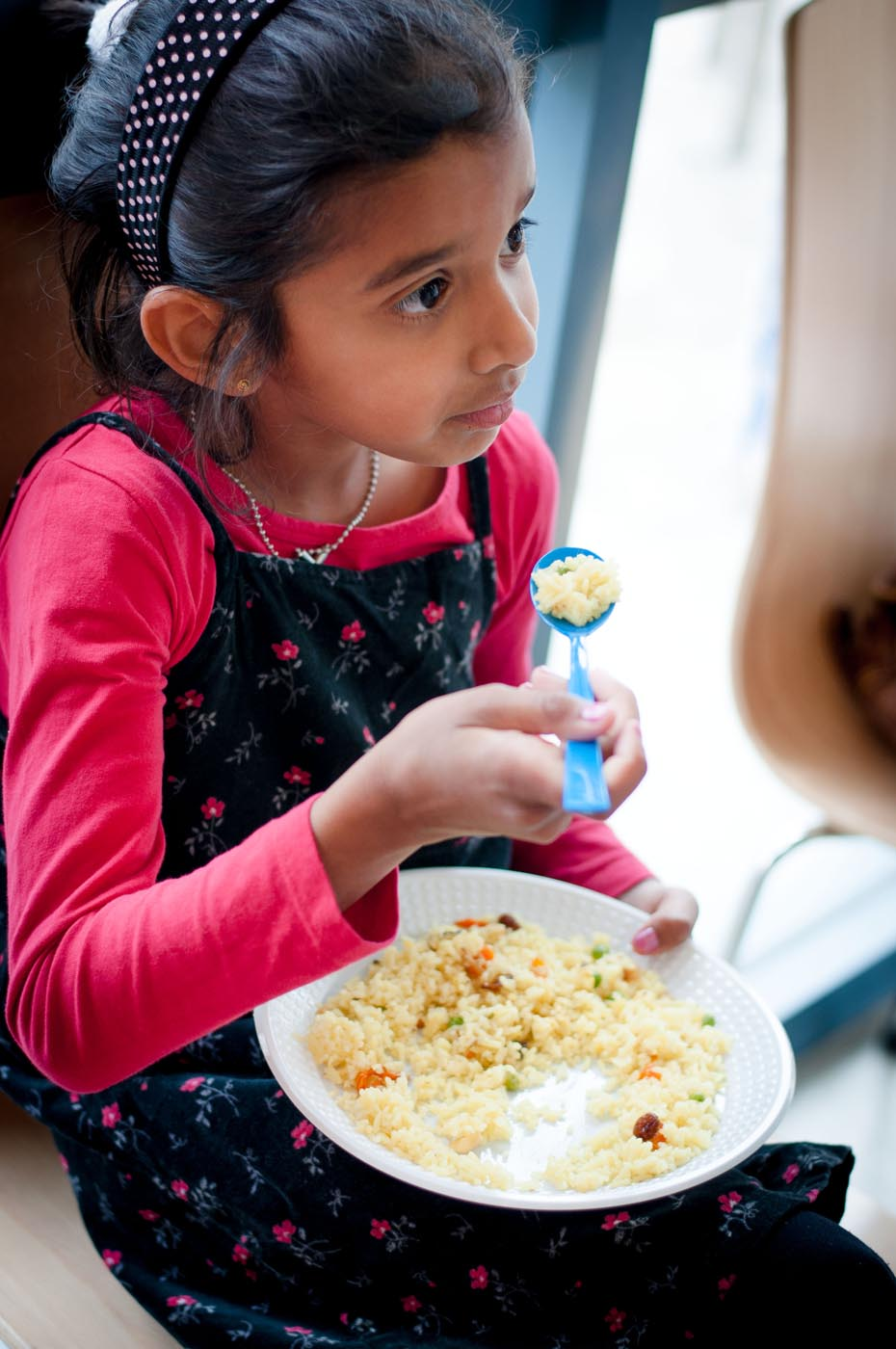Photo showing a young girl sitting down eating some fried rice from a plate with a plastic spoon - click to view larger image