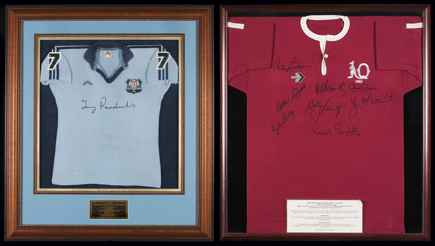 Two framed football jerseys. The jersey on the left is pale blue; the jersey on the right is maroon. - click to view larger image