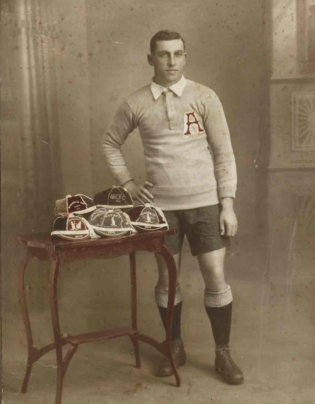 Studio photo of a man dressed in a football uniform. He stands beside a small table with various football caps on it. - click to view larger image
