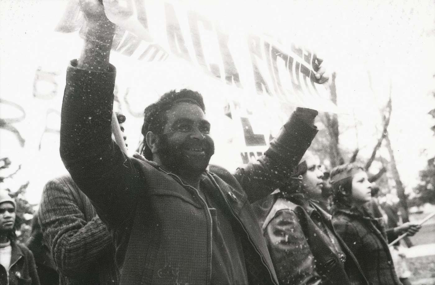 Black and white photo of a protest march with banners.