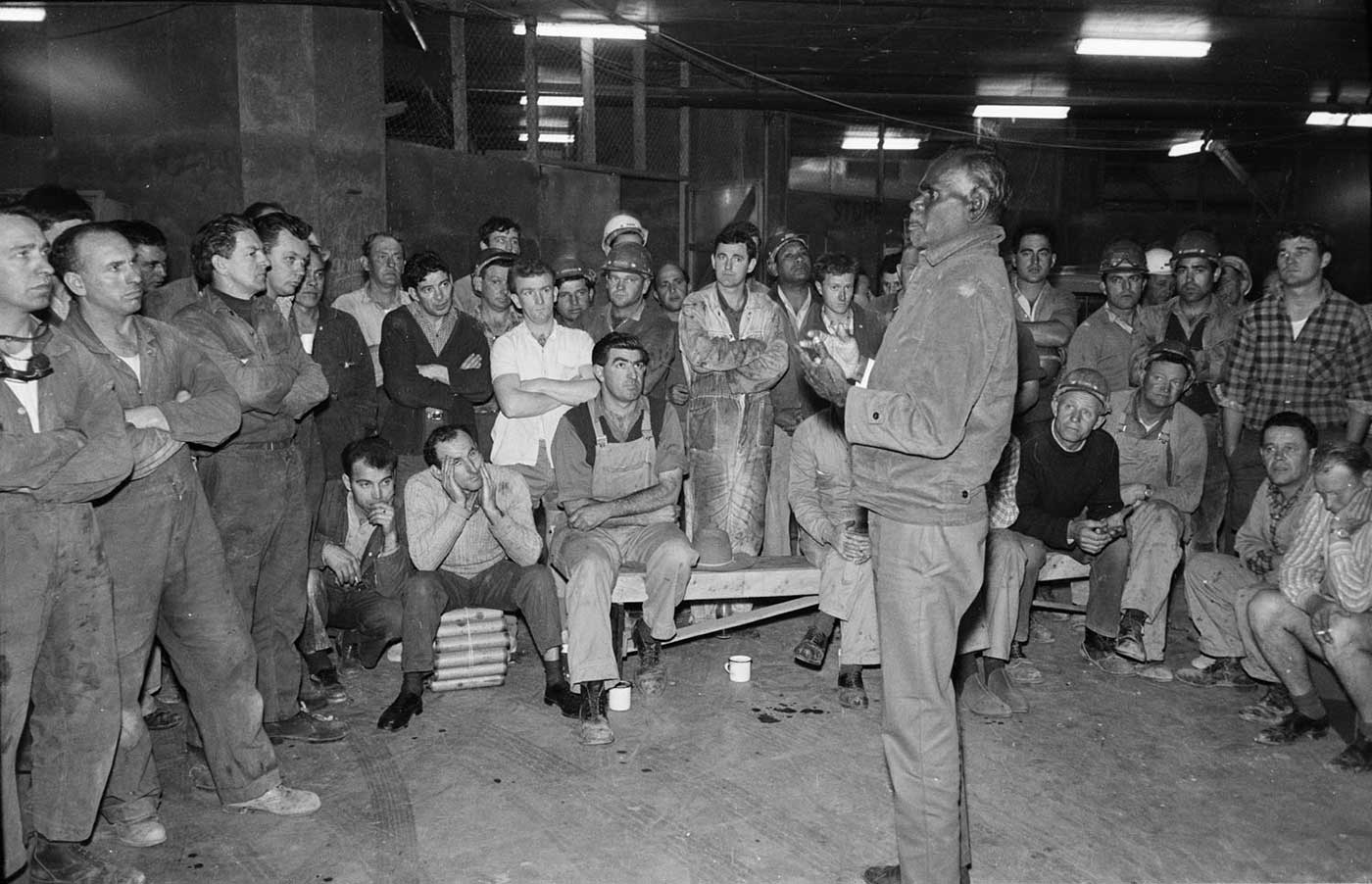 Black and white photo of a man speaking to a large group of trades people. - click to view larger image