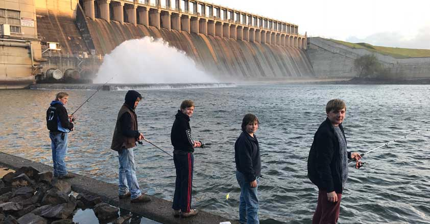 Five teenagers are holding fishing rods and standing on a cement ledge of a dam.