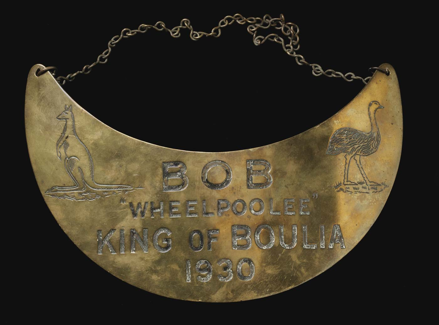 Crescent-shaped breastplate with chain at top, engraved with text 'Bob 'Wheelpoolee', King of Boulia, 1930' and images of a kangaroo and emu. - click to view larger image