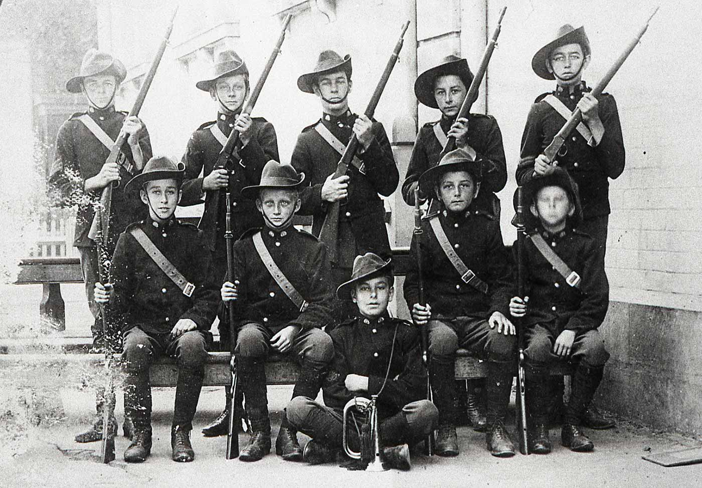 Black and white photograph showing a group of boys dressed in military uniforms and holding guns.