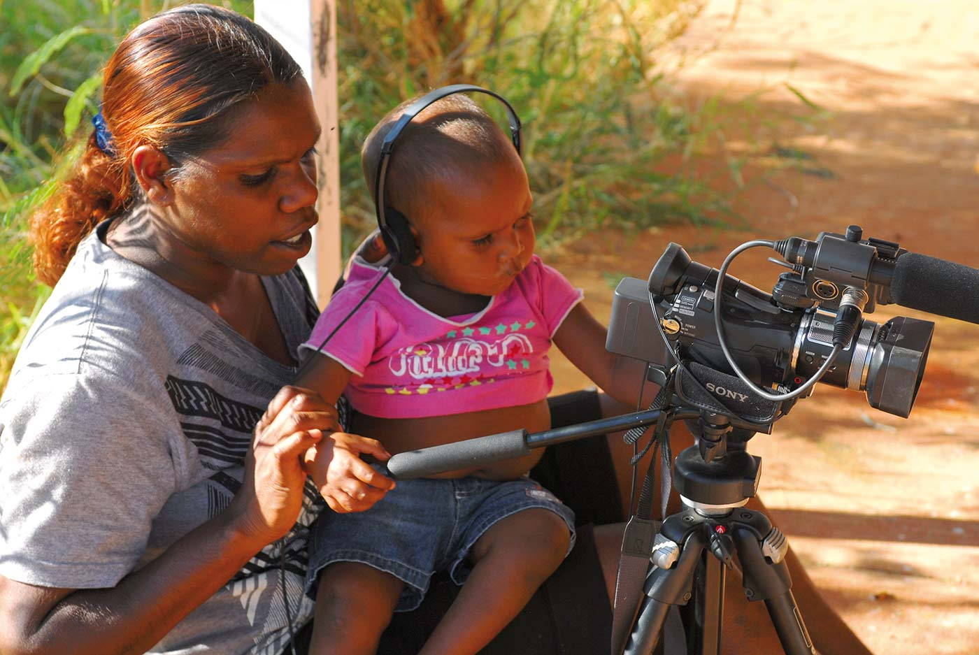 A young woman is showing a toddler who is wearing headphones and sitting on the woman's lap a film camera mounted on a tripod. - click to view larger image