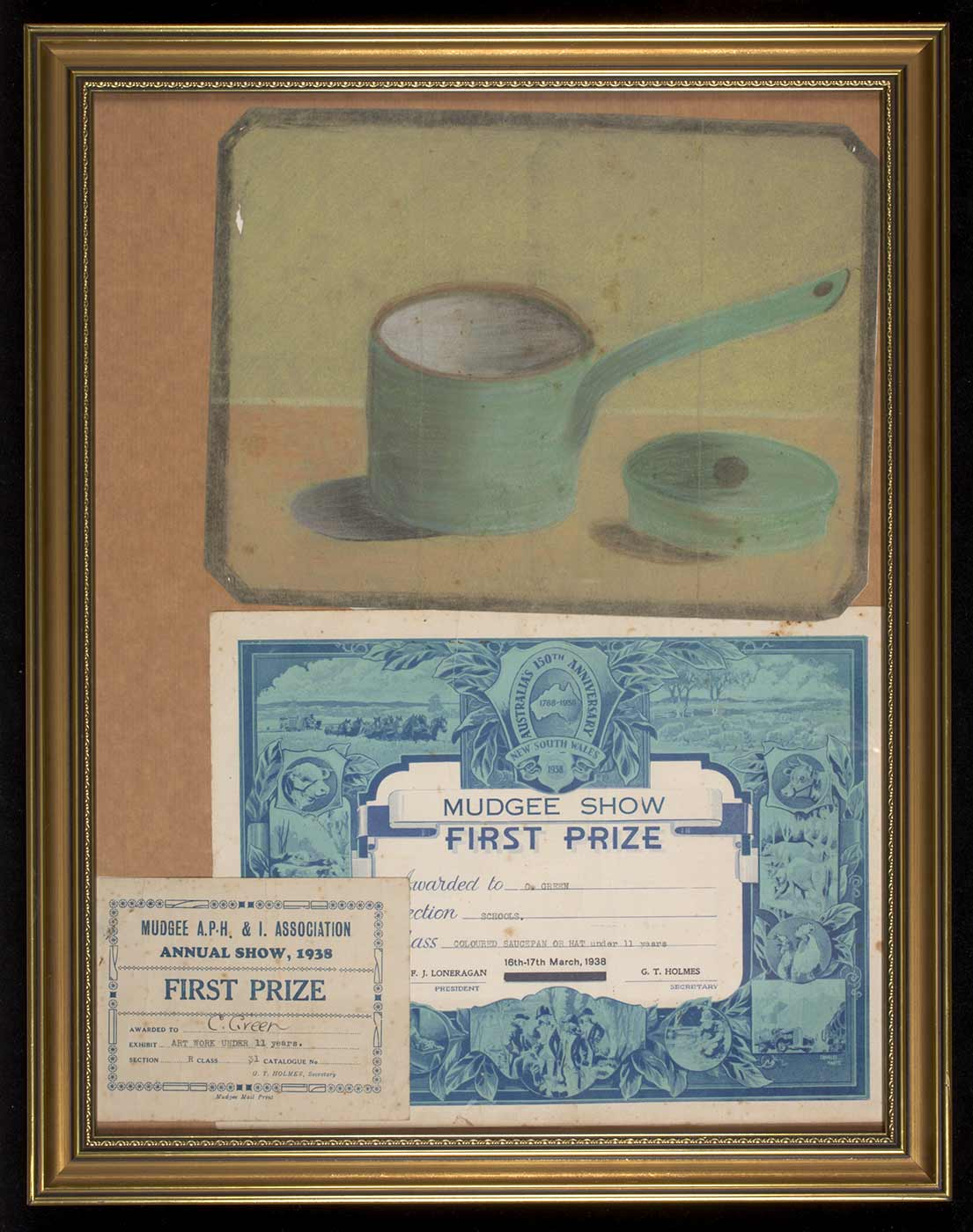 A child's painting of a green saucepan and lid, framed with two certificates below. The larger certificate, white with an ornate blue border depicting agricultural scenes, reads: 'MUDGEE SHOW / FIRST PRIZE / Awarded to C. GREEN / Section SCHOOLS / Class COLOURED SAUCEPAN OR HAT under 11 years / 16th-17th March, 1938 / PRESIDENT F. J. LONERGAN / SECRETARY G. T. HOLMES'. A smaller blue and white certificate in the bottom right reads: 'MUDGEE A.P.H. & I. ASSOCIATION / ANNUAL SHOW, 1938 / FIRST PRIZE / AWARDED TO C. Green, EXHIBIT ART WORK UNDER 11 years / SECTION R CLASS 31 / G. T. HOLMES, Secretary'. - click to view larger image