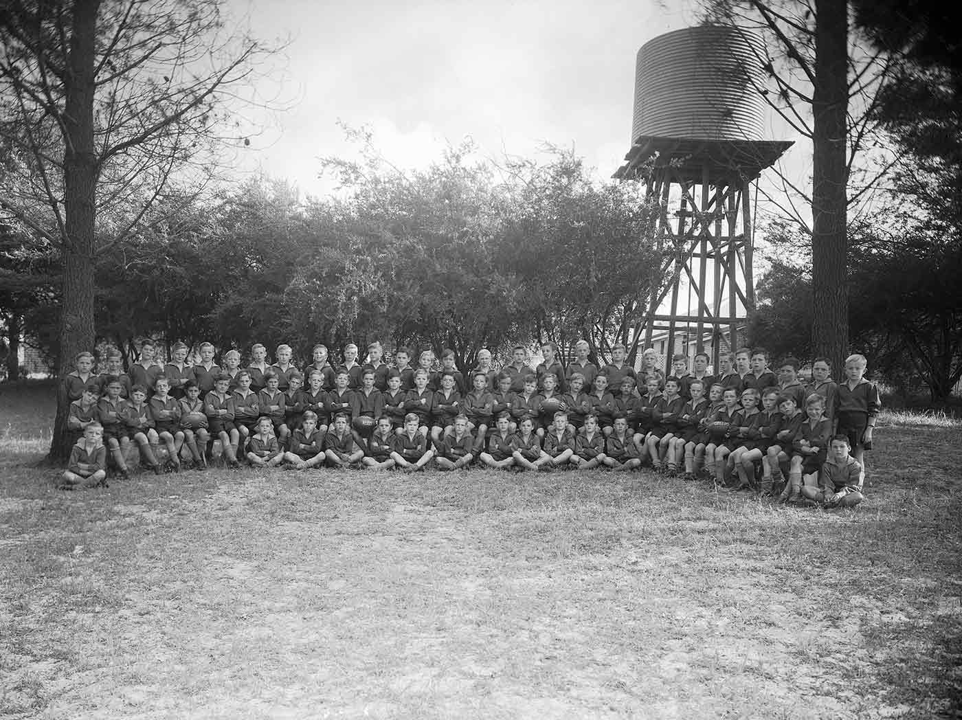 Black and white photo showing about 100 young boys in three rows, with two rows standing and one row sitting at the front. The boys have their arms folded and legs crossed. Three boys hold footballs. A corrugated iron water tank atop a wooden stand and a row of trees can be seen behind. - click to view larger image