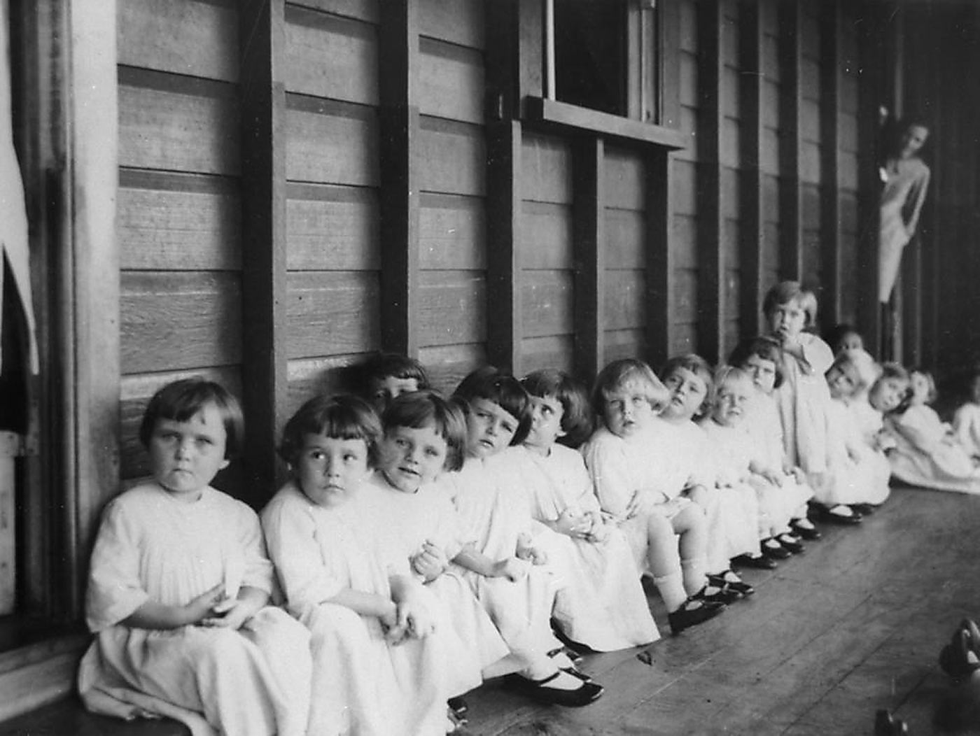 Black and white photograph showing a group of young girls sitting on a timber verandah. The girls wear long, white dresses and black shoes. An older person leans out of a door at the far end of the photograph. - click to view larger image