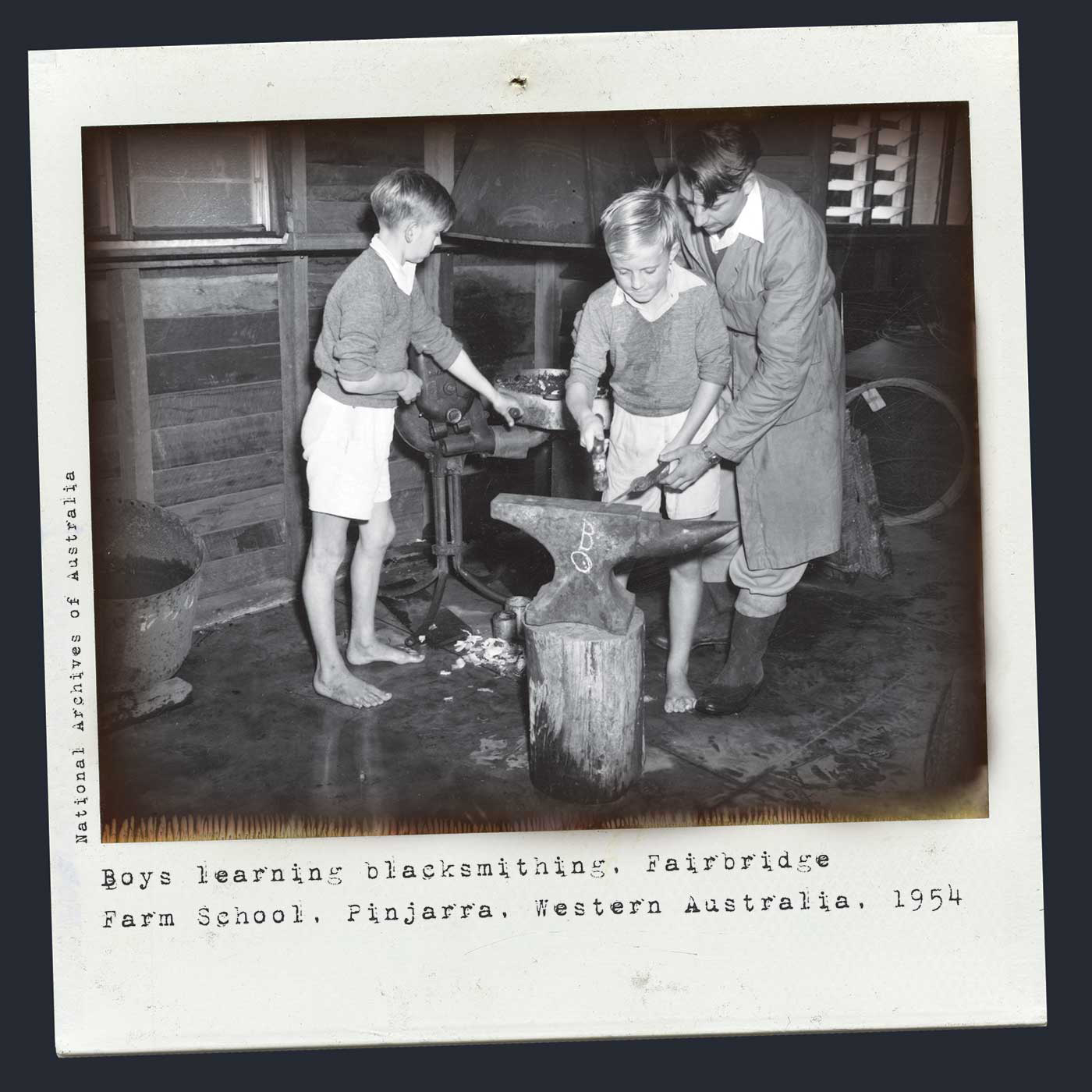 Polaroid photograph showing two young boys and an older man. The boys are barefoot and wear uniform jumpers and shorts. A man in a grey dustcoat stands over one of the boys, helping him hammer a piece of metal at an anvil. The other boy works the forge at the rear. Typewritten text below reads 'Boys learning blacksmithing, Fairbridge Farm School, Pinjarra, Western Australia, 1954'. 'National Archives of Australia' is typed along the left side. - click to view larger image