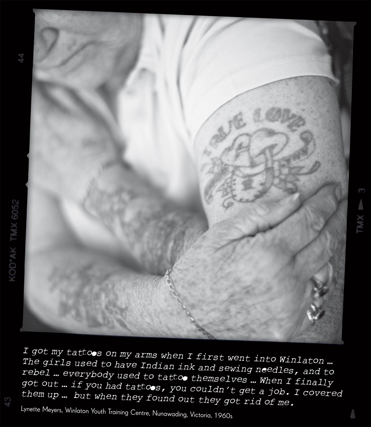 Black and white photo of a woman's tattooed arms.  The photo caption reads 'I got my tattoos on my arms when I first went into Winlator ... The girls used to have Indian ink and sewing needles, and to rebel ... everybody used to tattoo themselves ... When I finally got out ... if you had tattoos, you couldn't get a job.  I covered them up .. but when they found out they got rid of me' attributed to 'Lynette Meyers, Winlaton Youth Training Centre, Nunawading, Victoria, 1960s'. - click to view larger image