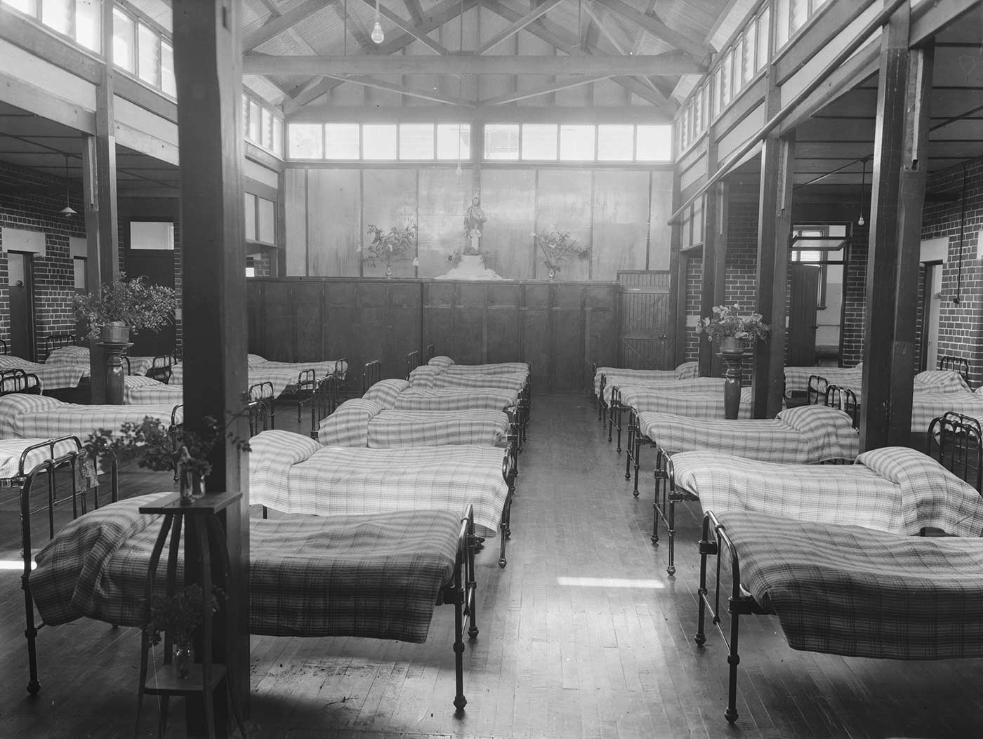 Black and white image showing a large room with high ceilings, filled with five rows of single, metal beds. Each is covered with a checked bedspread. Three small high tables stand in the room, with bases of flowers on top. Another two vases of flowers and  a religious statue sit on top of cupboards at the far end.