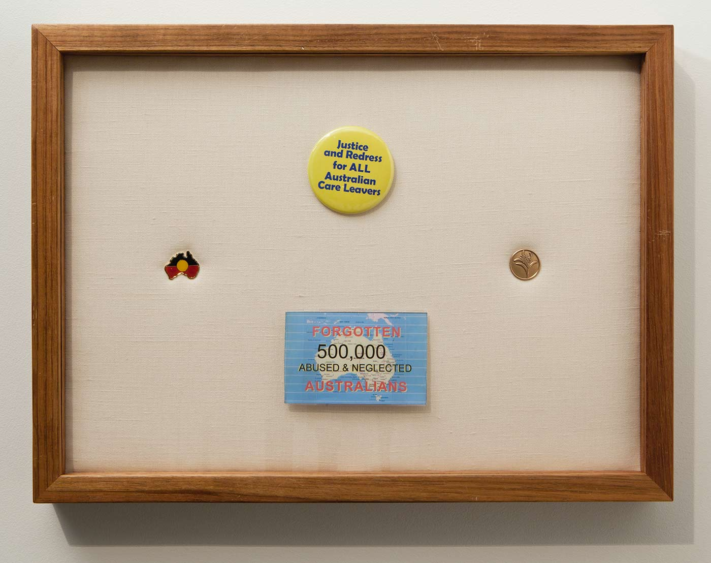 Photograph of a timber frame with four badges mounted on a soft background. An Aboriginal flag in the shape of Australia is at left, the top badge is cirucular and yellow and printed with the words 'Justice and Redress for ALL Australian Care Leavers'. A blue printed rectangular badge below reads 'FORGOTTEN / 500,000 / ABUSED & NEGLECTED / AUSTRALIANS'. A circular gold badge at right is embossed with a wattle emblem. - click to view larger image