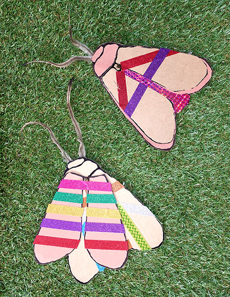 Colour photo of two colourful decorated paper moths.