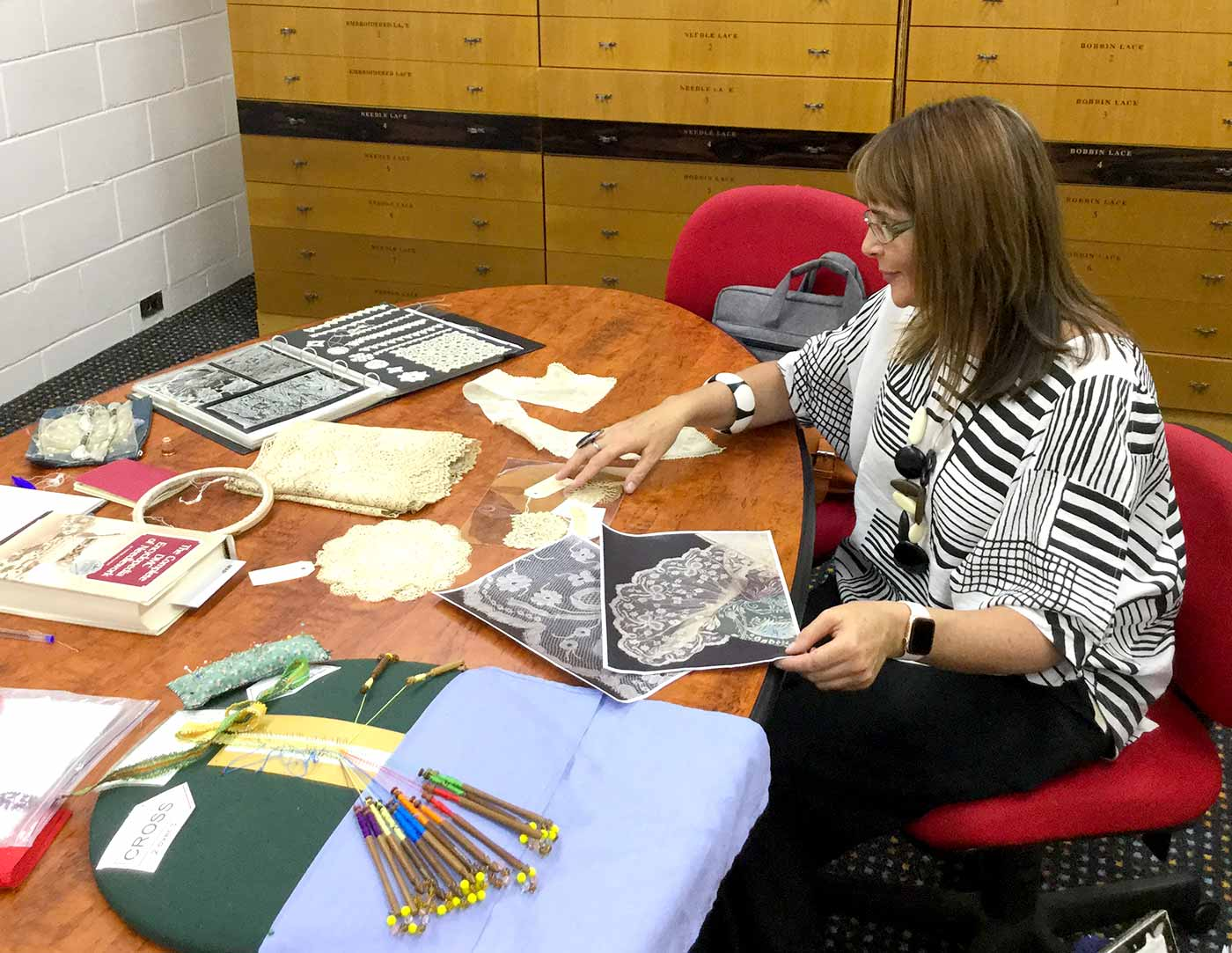A woman is sittings at table with various items related to textiles including samples and photocopies of lace.