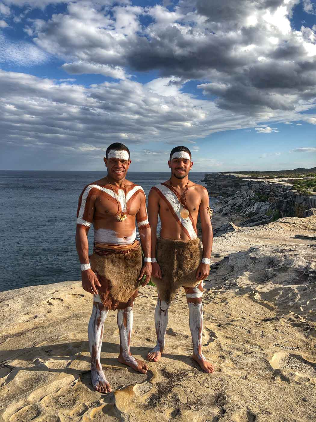 Two young men stand atop rocks overlooking the ocean. They wear animal skins and white body paint. - click to view larger image