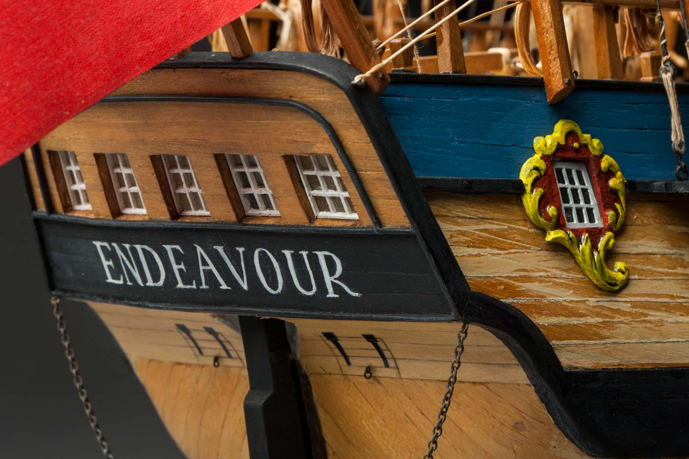 Detail image showing the back of a model wooden sailing ship. 'Endeavour' is painted under a series of five windows. - click to view larger image