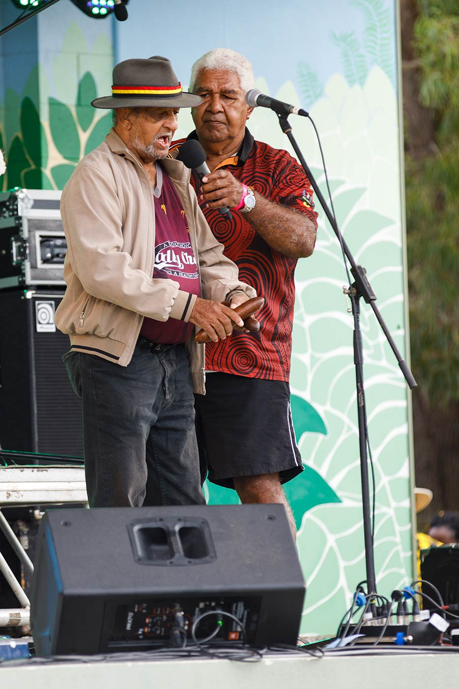 Colour photo of two men on a stage. One of them is singing into a microphone and holding instruments that are wooden sticks. - click to view larger image