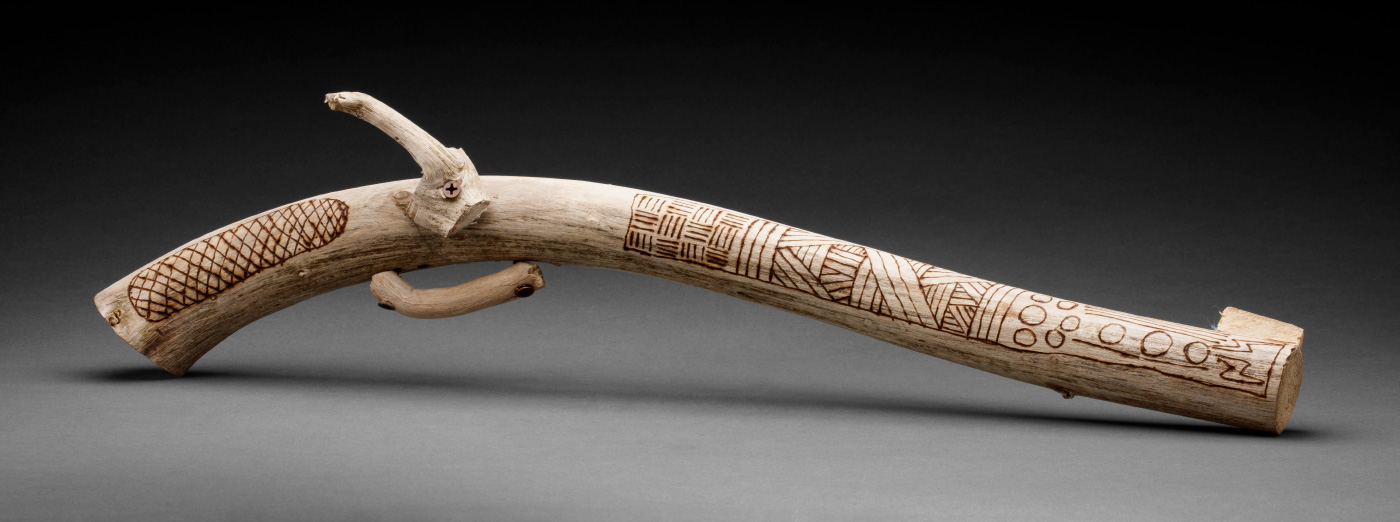 An artwork in the shape of a handgun, made from driftwood featuring pokerwork design. - click to view larger image