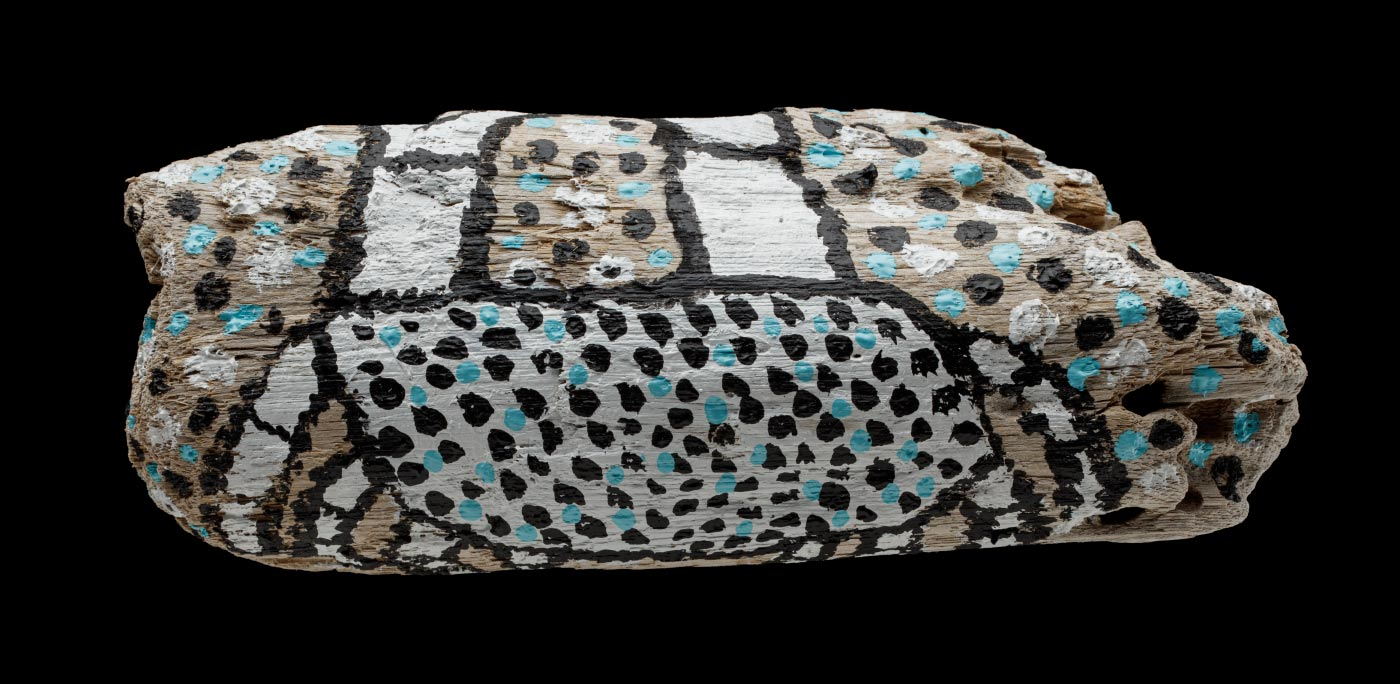 An acrylic painting on driftwood featuring a white crab with a black outline, body filled with blue and black dots. Surrounding the crab are also black, blue and white dots. - click to view larger image