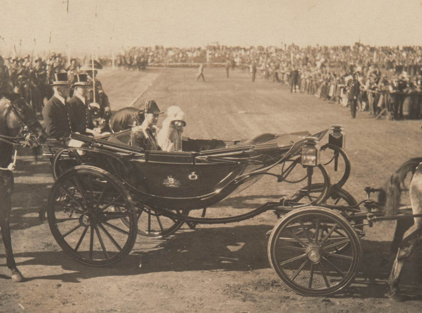 A couple seated in a horse-drawn carriage with crowds in the distance. - click to view larger image