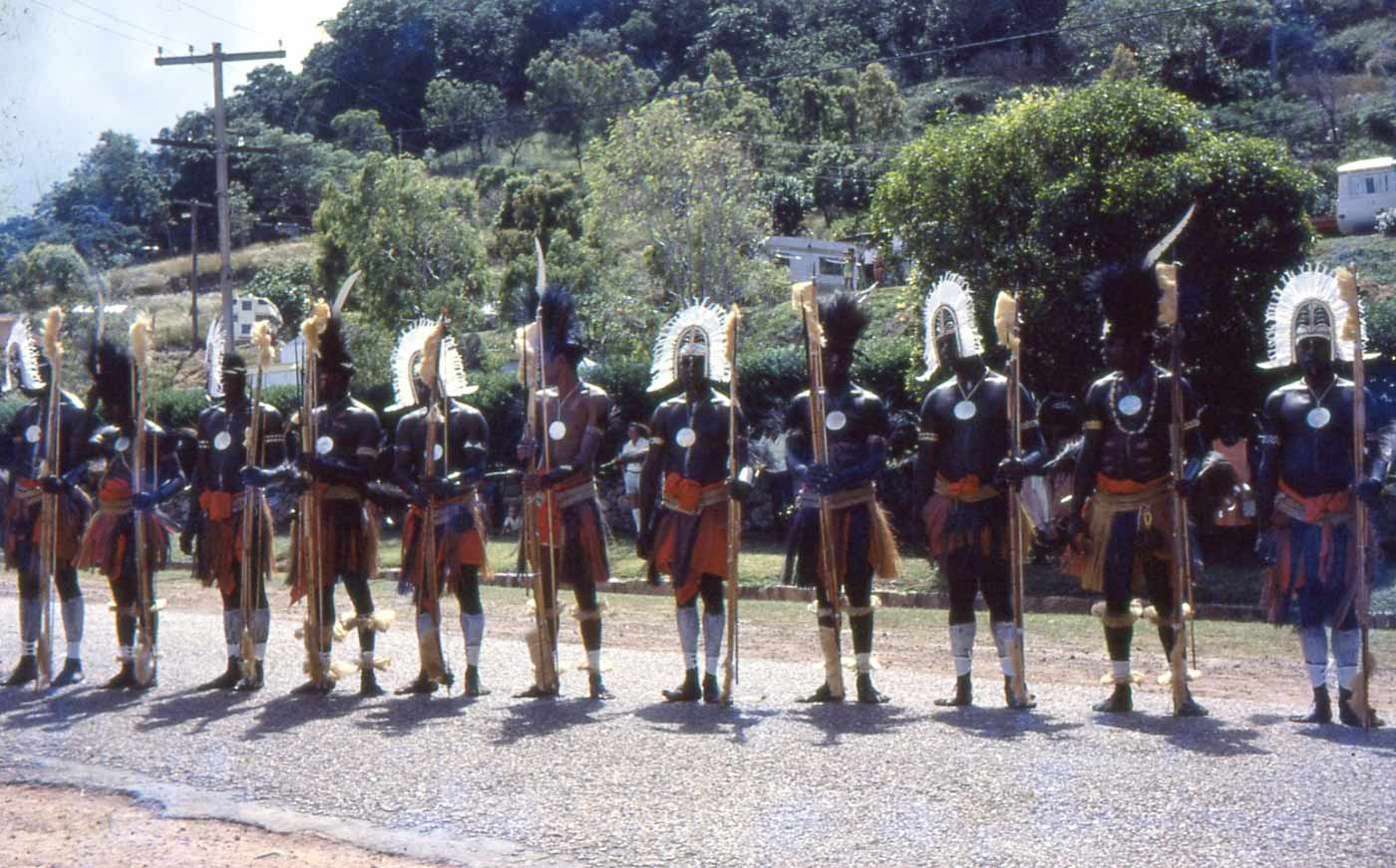Colour photo of a group of men in traditional costume standing in a straight line on a bitumen road. - click to view larger image