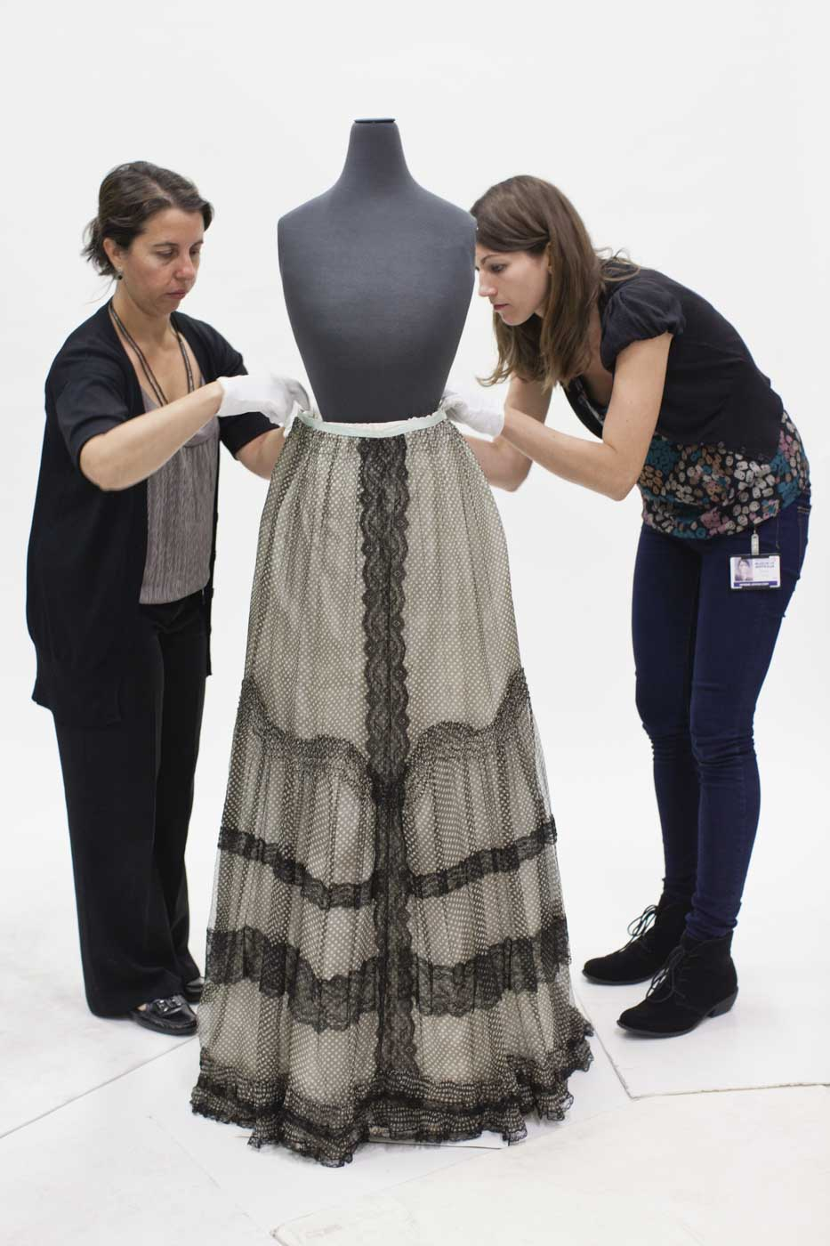 Two conservators adjust a skirt on a mannequin. - click to view larger image