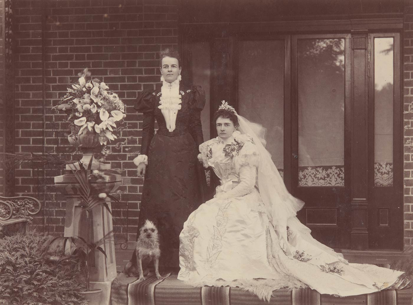 Black and white photo of a woman in a wedding dress and veil, seated. A woman in a dark dress stands at her left. A small terrier dog sits at her feet.
