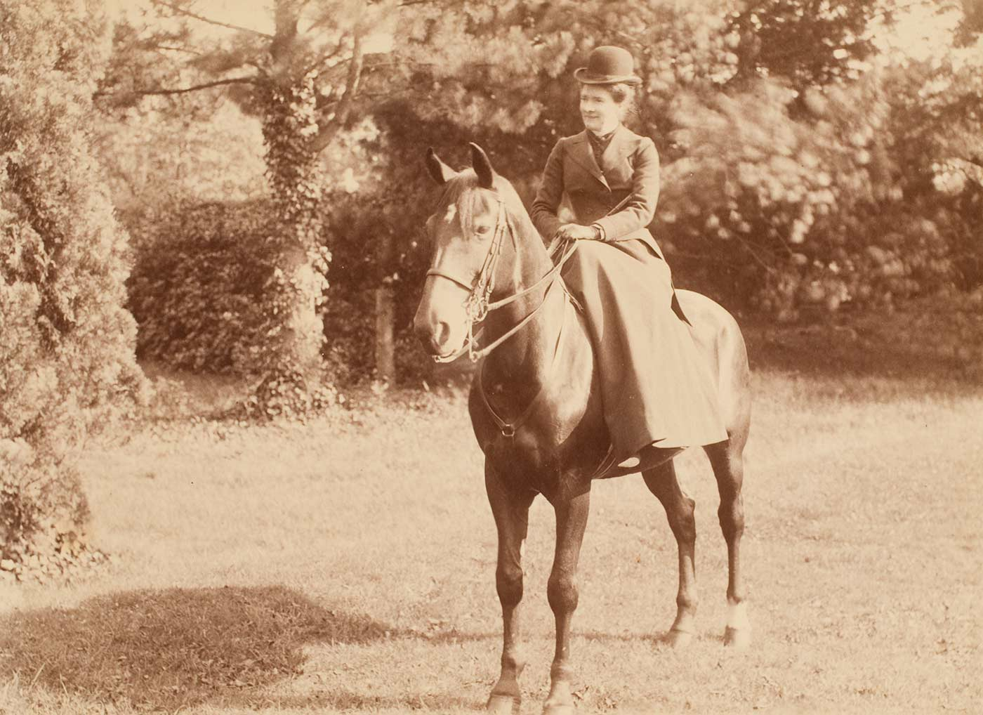 A black and white photograph that depicts Constance Faithfull sitting side-saddle on a horse.