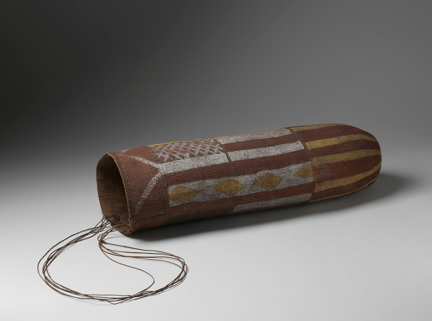 A cylindrical fibre basket with a string handle. The basket has been painted with ochre. - click to view larger image